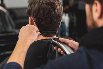 Hairdresser cutting male hair by machine