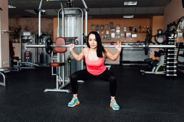 Beautiful fitness woman lifting barbell.