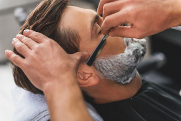 Professional barber getting rid of male stubble