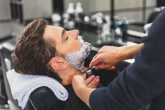 Skillful hairdresser using blade for shaving beard