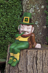 Leprechaun smiling and sitting on tree trunk with pipe/Leprechaun smiling and sitting on a tree trunk with pipe, green and gold suit and hat