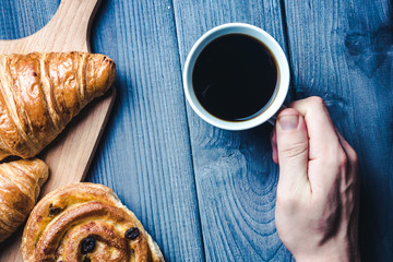 Hand holding white coffee cup on blue wooden table with croissant.