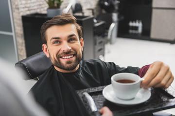 Happy guy drinking beverage at beauty salon