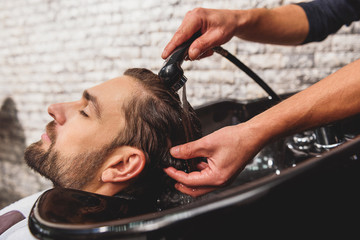 Professional barber undergoing hairwash at salon