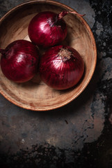 red onions in an old wooden bowl on a grunge background of old metal. close up, top view