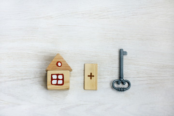 individual construction property/ wooden model of house plus key on light wood surface top view