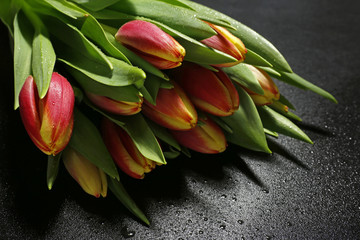 bouquet of tulips with water drops on black background