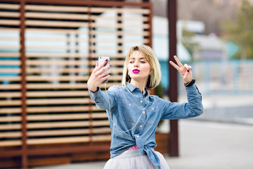 Beautiful stylish blond girl in tulle skirt and denim shirt with purple lips is having fun and makes selfie with a kiss face and with victory sign fingers with striped brown wooden balks behind.