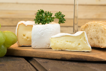 Verschiedene Camembert Sorten angerichtet, mit Petersilie und Baguette