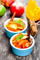 Caramelized  pumpkin and apple in small pot on wooden table