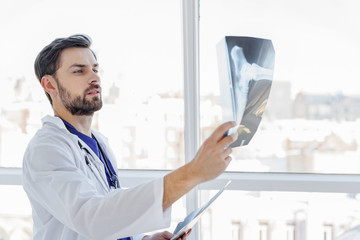 Smart male general practitioner looking at radiograph