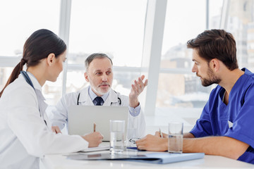 Mature general practitioner explaining something to interns