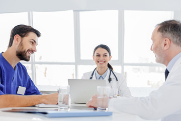 Cheerful doctors discussing human health with satisfaction