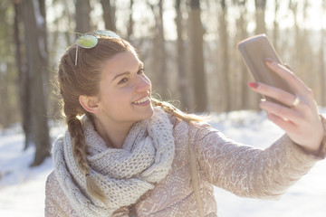 Girl taking selfie by mobile phone on snow