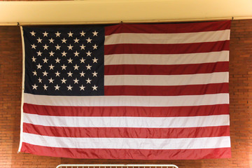 large american flag hanging against a red brick background