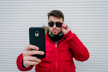 A young man in glasses makes selfie