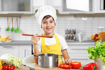 Cute boy cooking in kitchen at home