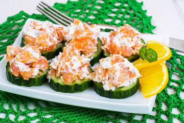Appetizer with salmon, cucumber and goat cheese