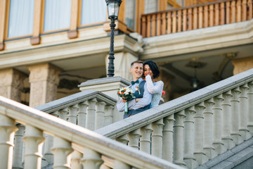 Happy bride and groom hugging on stairs of mansion