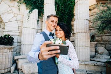 Wedding travel selfie. Groom and bride takes selfie on mobile phone in Greece
