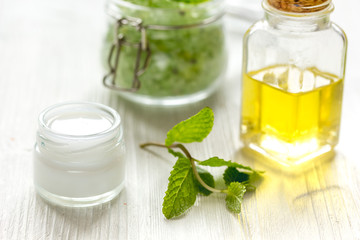 organic cosmetics with herbal extracts of mint on wooden background
