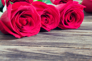 red three roses on a wooden background