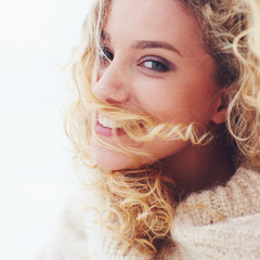 portrait of beautiful delighted woman with curly hair and adorable smile