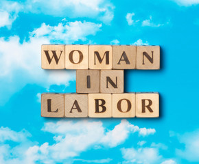 The word woman in labor on the sky background