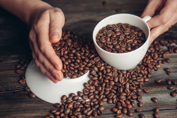 Coffee beans on a light saucer and a cup in hand