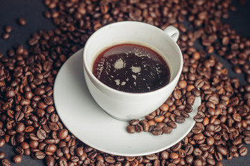 cup with a dark drink and coffee beans on the table