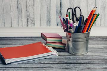 notebooks on the table and an iron pail with pencils