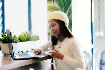 Beautiful girl networking in a cafe with laptop computer