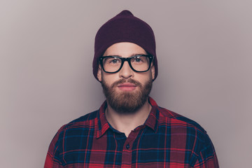 Portrait of young confident serious hipster man in glasses