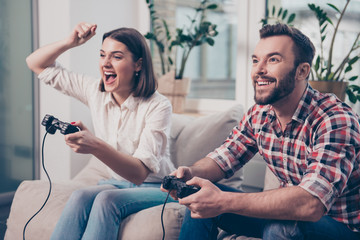 Two excited happy lovers playing video game