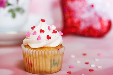 Valentine Cupcake topped with vanilla frosting and heart sprinkles