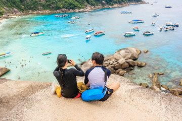 Happy Loving couple on a cliff view tropical beautiful crystal clear sea at tropical island, Similan Islands National Park, Phang Nga, Thailand
