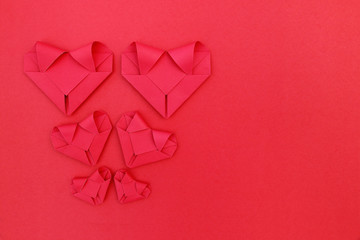 six folding red paper hearts on red for valentine pattern and ba