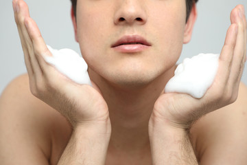 young man washing his face with cleansing foam, men's skincare concept, acne treatment