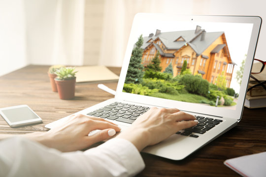 Online shopping concept. Woman looking for house on real estate market website