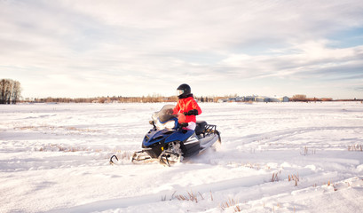 A teenage girl in bright colored winter gear and a helmet snowmobiling across a snow covered field with a farmyard in the background in a winter landscape