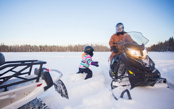 A four year old girl in winter coat and ski pants wearing a helmet walking through deep snow toward her father on a snowmobile parked in a white snow covered field