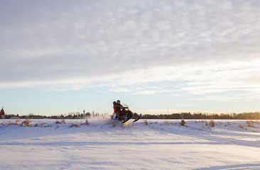 A teenage girl on a snowmobile with her father having fun ramping over a small hill in a winter landscape