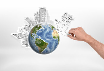 Man's hand holding cartoon funny monster going to attack city put around the globe on