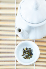 Green tea leaves and an white teapot, top view