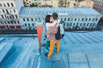 Young happy couple hugging on the roof in St. Petersburg and happy