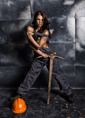 sexy female miner worker with pickaxe, in coveralls over his naked body. erotic industry concept