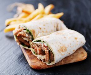 greek gyro wrap cut in half and served with fries