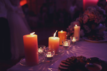 lighted round candles stand on the table in the dark