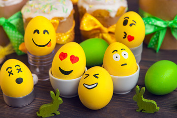 Easter eggs with  smiley faces, on wooden background