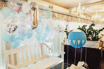 White bench decorated with blue balloons stands in restaurant's